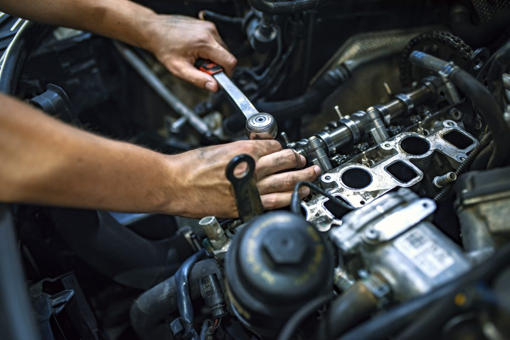 Photo of mechanic's hands tinkering with an engine.